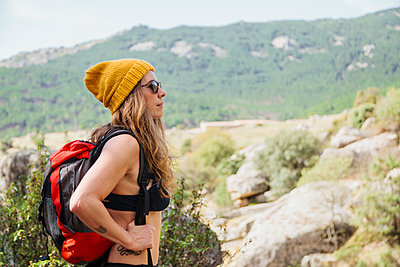 Trekker with backpack admiring view while standing on mountain at La Pedriza, Madrid, Spain - p300m2226340 by Manu Reyes