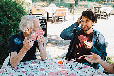 Smiling male caretaker playing cards with senior man and woman at table in back yard - p426m2074386 by Maskot