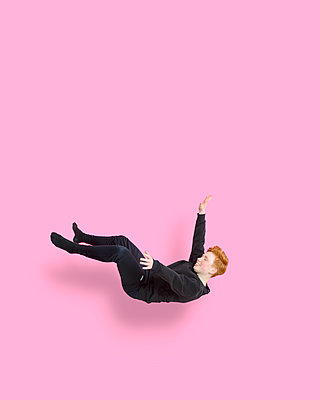 Jumping girl in front of pink background - p427m2272307 by Ralf Mohr