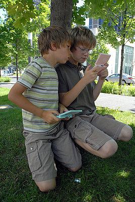 Zwei Jungen beim Nintendo DS spielen - p567m667702 von AURELIAJAEGER