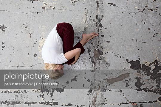 Eine Frau liegt in Embryostellung auf dem Boden  - p1301m1582537 von Delia Baum