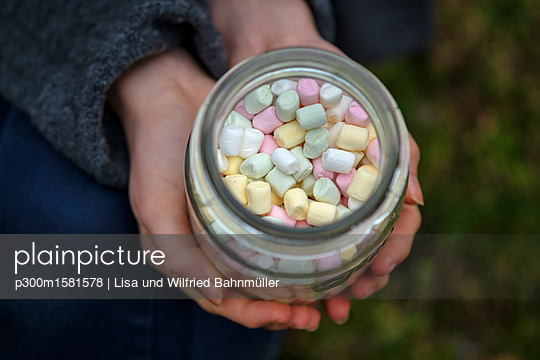 Hands holding glass of marshmallows, close-up - p300m1581578 von Lisa und Wilfried Bahnmüller