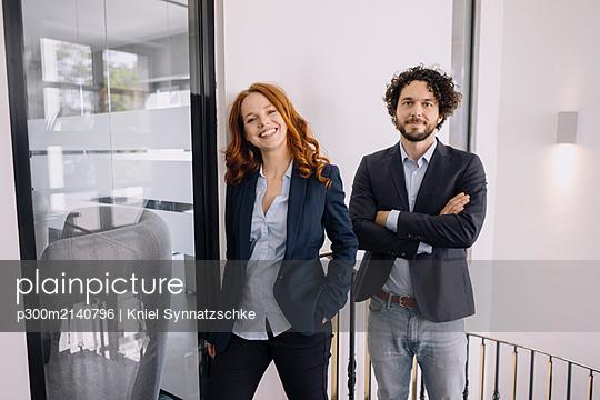 Portrait of confident businessman and businesswoman in office - p300m2140796 by Kniel Synnatzschke