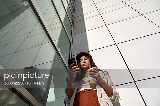 Beautiful woman with reusable cup using smart phone while standing against wall - p300m2256718 by Veam