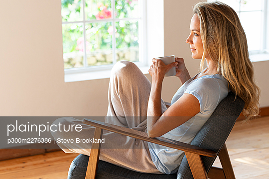 Woman day dreaming while holding coffee mug on chair at home - p300m2276386 by Steve Brookland