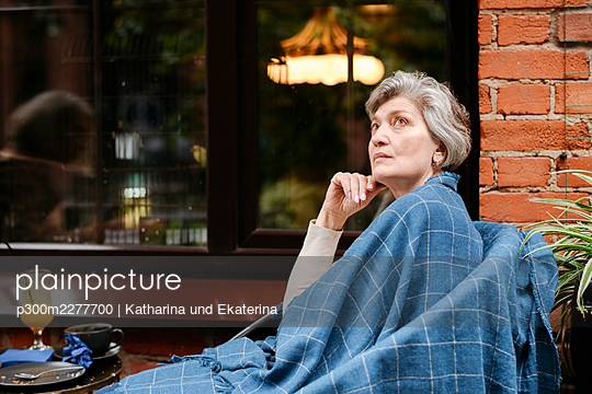 Thoughtful mature woman wrapped in blanket looking up - p300m2277700 by Katharina und Ekaterina