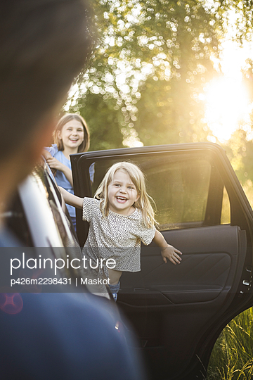 Portrait of mother, father and two daughters standing by car at electric vehicle charging station - p426m2298431 by Maskot