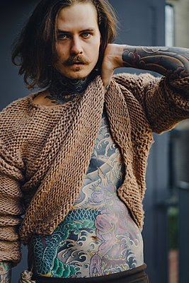 Handsome tattooed sexy man with long hair and mustache outdoors - p1166m2147647 by Cavan Images