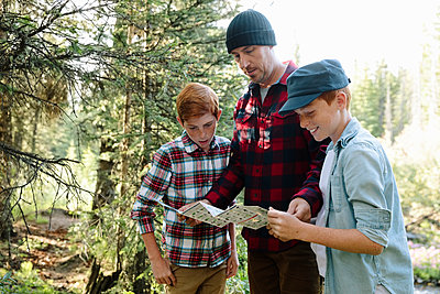 Father and sons looking at trail guide in woods - p1192m2129260 by Hero Images