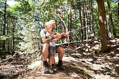 Father and son shooting with bow and arrow in the forest - p300m1499438 by Michelle Fraikin