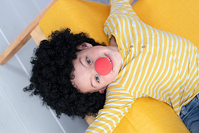 7 year old boy with red clown nose and black hair on yellow couch - p300m2170388 von Epiximages