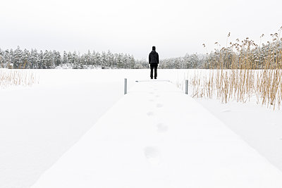 Mature woman standing next to frozen lake in Ostergotland, Sweden - p352m2120016 by Åke Nyqvist