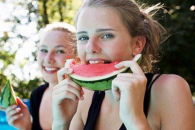 Two teenage girls eating watermelon slices in garden - p429m1080040f by Christine Schneider