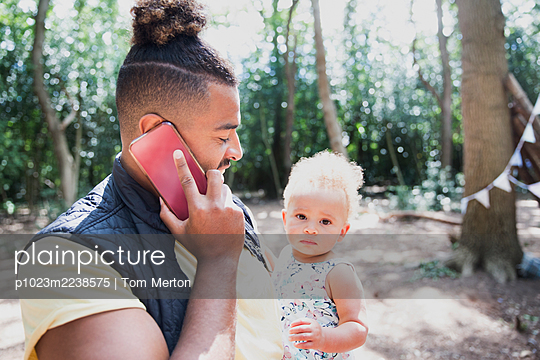 Father holding toddler daughter and talking on smart phone in woods - p1023m2238575 by Tom Merton