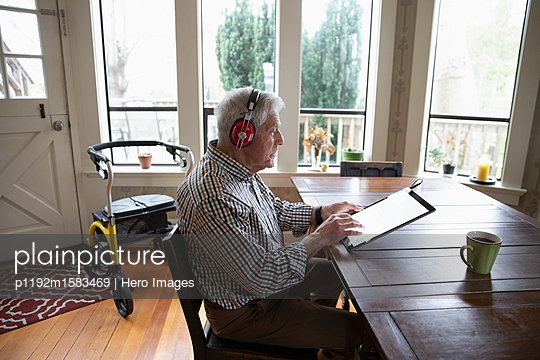 Senior man with headphones using digital tablet at dining table - p1192m1583469 by Hero Images