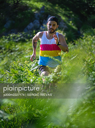 Mid adult man running between grass on mountain at forest - p300m2227174 by SERGIO NIEVAS