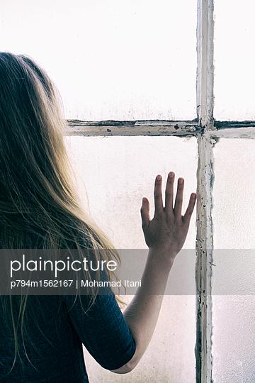 Frau am Fenster, Hand berührt Glas - p794m1562167 von Mohamad Itani