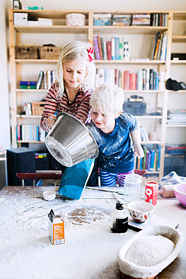 Brother and sister playing with flour at home - p1185m1015947f by Astrakan