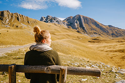 Young woman on wooden bench, Durmitor National Park, Unesco World Biosphere Reserve - p1600m2184188 by Ole Spata