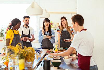 Friends in a cooking workshop listening to instructor - p300m1588165 von Bonninstudio