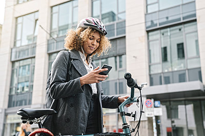 Woman with bicycle and smartphone in the city, Berlin, Germany - p300m2143460 by Hernandez and Sorokina