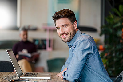 Smiling male entrepreneur with laptop leaning on table at work place - p300m2273932 by Daniel Ingold
