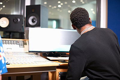 Rear view of young male college student at sound mixer in recording studio - p429m1494618 by Peter Muller