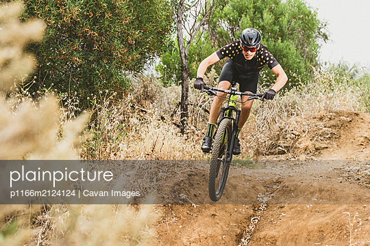 Full body of mountain bike cyclist doing a jump in forest - p1166m2124124 by Cavan Images