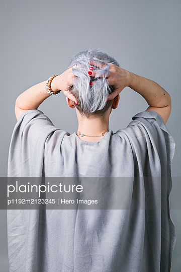 Woman with hands in short hair - p1192m2123245 by Hero Images