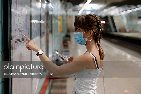 Woman with protective face mask looking at rout map of train on platform during pandemic - p300m2264699 by Albert Martínez