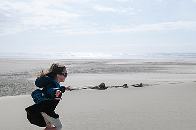 Side view of girl with arms outstretched running on beach against sky - p1166m1485525 by Cavan Images