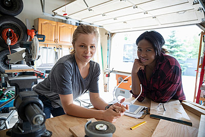 Portrait confident young women friends woodworking, planning in garage - p1192m2009535 by Hero Images