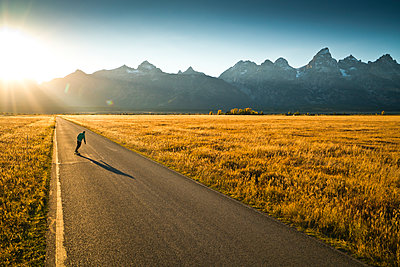 A skateboarder riding towards the sunset in Wyoming. - p1424m1500833 by Rob Hammer