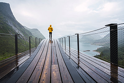 Norway, Senja island, rear view of man standing on an observation deck at the coast - p300m2042273 by Kike Arnaiz