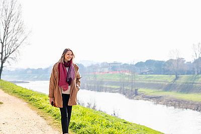Smiling woman walking by river bank - p300m2275076 by Emma Innocenti