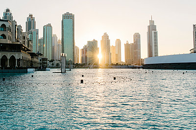 Sunset over city skyline, Dubai, United Arab Emirates - p555m1410087 by Aaron Greene