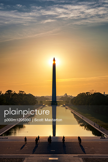 USA, Washington DC, view to Washington Monument at sunrise with soldiers training in the foreground