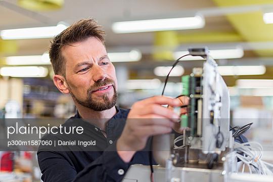Man in factory working on device - p300m1587060 von Daniel Ingold