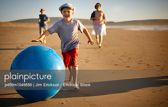 Portrait of a smiling young boy chasing a swiss ball along a sandy beach with his family - p456m1049556 by Jim Erickson / Erickson Stock