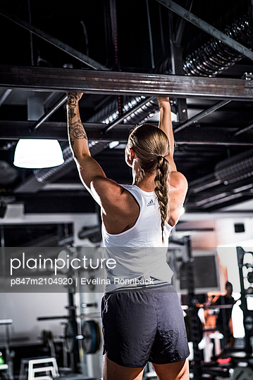 Rear View Of An Athletic Woman Doing Pull-ups In Gym   - p847m2104920 by Evelina Rönnbäck