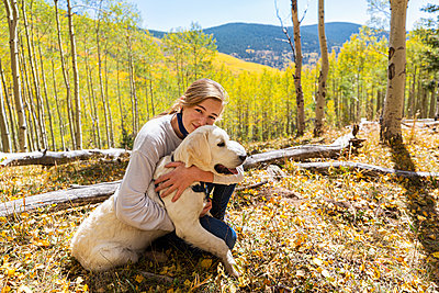 teenage girl embracing her English Cream Golden Retriever - p1100m2220351 by Mint Images