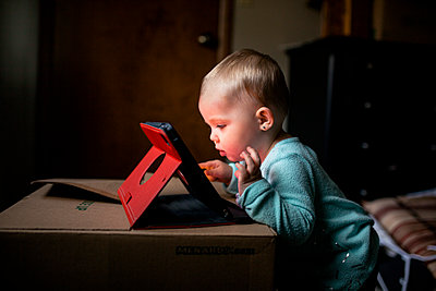 Side view of baby girl using tablet computer while standing by box at home - p1166m1521706 by Cavan Images