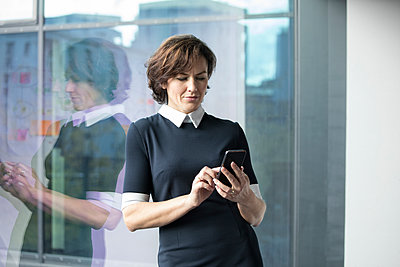 Businesswoman husing cell phone at the window - p300m1228725 by Rainer Berg