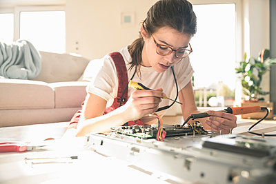 Young woman working on computer equipment at home - p300m2103884 by Uwe Umstätter