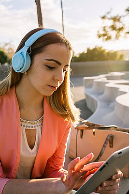 Young woman with headphones using digital tablet outdoors - p300m2243367 by Xavier Lorenzo