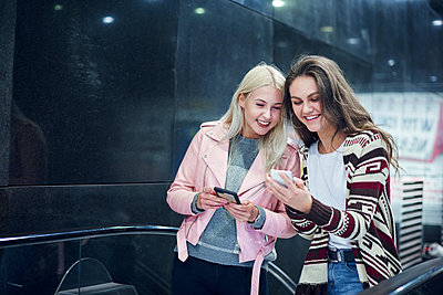 Two young women moving up underground station escalator  looking at smartphone - p429m1513804 by Gpointstudio
