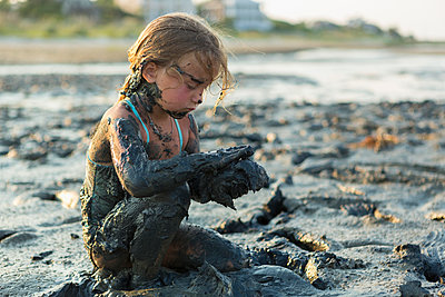 Caucasian girl covered in mud playing on beach - p555m1522774 by Marc Romanelli
