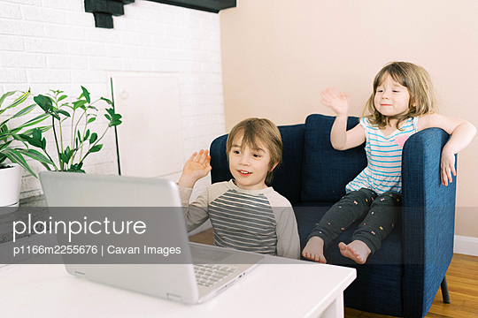 Two small children at laptop in living room during video call online - p1166m2255676 by Cavan Images