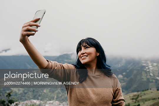 Smiling mid adult woman taking selfie through mobile phone in front of sky - p300m2274466 by MORNINGVIEW AGENCY