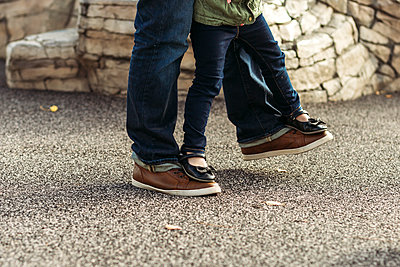 Low section of daughter walking on father's feet - p1166m1473636 by Cavan Images